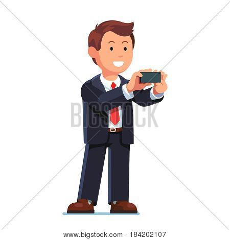 Smiling businessman in black suit standing with mobile phone in his hands and taking photo or shooting a video. Flat style modern vector illustration isolated on white background.