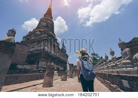 Young woman traveler with sky blue backpack and hat looking Wat Yai Chai Mongkol (or Mongkhon) temple background from Ayutthaya near Bangkok Thailand. Traveling in Ayutthaya near Bangkok Thailand