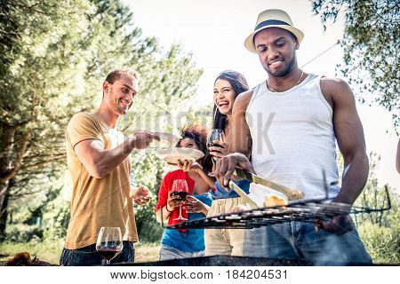 Happy multiracial friends having fun at picnic barbecue garden party