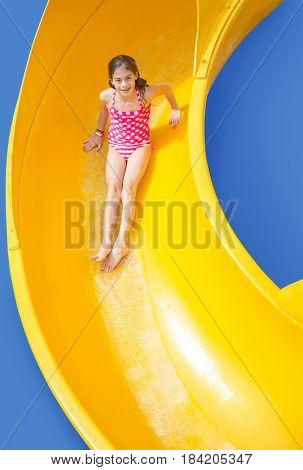Cute girl riding down a yellow water slide at an outdoor waterpark. Lots of copy space and fun colors