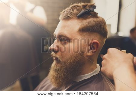 Barber styling beard with trimmer at barbershop, closeup. Male Barbershop