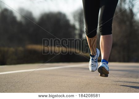 Fitness woman training and jogging in spring park, feet close up . Healthy lifestyle and sport concept