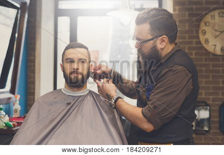 Barber make beard style haircut with trimmer hair clipper in barbershop, closeup of client's head. Hairstyle in male hair salon