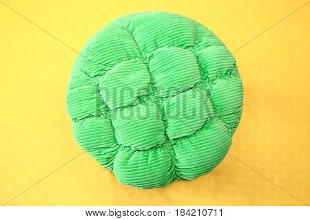 Details of a green ottoman on yellow background