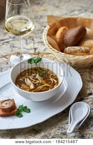 Asian cuisine. Mushroom soup with egg noodles served with toast, bread and white wine on marble background.