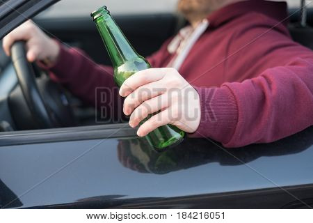 Drunk man driving his car and drinking alcohol