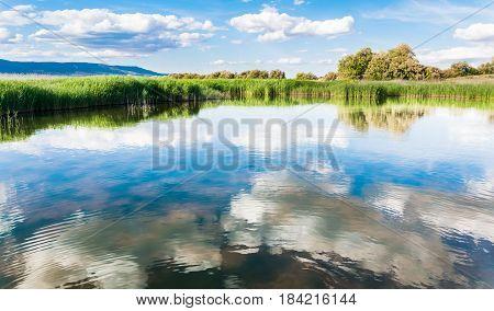 Reflejo de un cielo nuboso en el agua de una laguna, en un día primaveral.