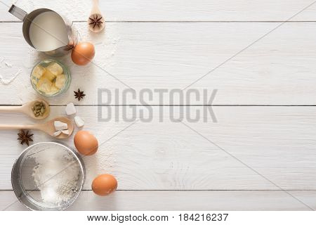 Baking background with copy space. Cooking ingredients for yeast dough and pastry, eggs, flour and milk on white rustic wood. Mockup for menu, recipe or culinary classes.