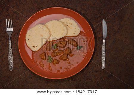 Traditional Hungarian Goulash Wit Dumplings On Plate On Rusty Metal Sheet
