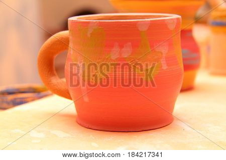 earthenware mug with handle colorized, pottery craft, moulding the pot with your hands, sculpting hands