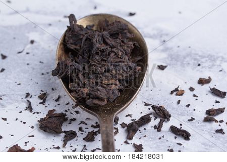 Leaves Of Black Tea In A Spoon On A White Background. Tea In An Antique Spoon.
