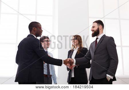Meeting Success Handshake Teamwork Concept. Multiethnic Business People In Light Office, Copy Space