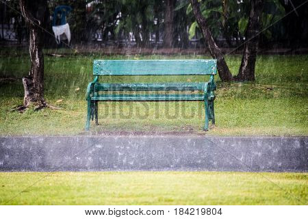 Rain with wooden chair in background .