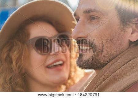 I am the happiest man. Cheerful middle-aged man is enjoying date with his lover. He is looking forward pensively and smiling. Woman is standing near him expressing happiness