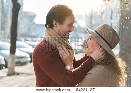 Love me tender. Smiling adult lovers embracing gently in the city. They are making googly eyes at each other. City on the background