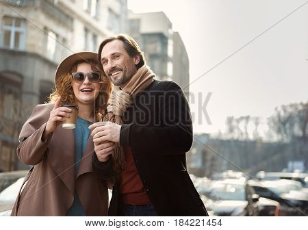 Look at that. Portrait of cheerful loving couple warming up by hot beverage outdoors. They are standing and looking forward with interest. Copy space in right side