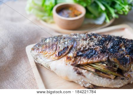 Close up tilapia grilled with vegetable on wood tray