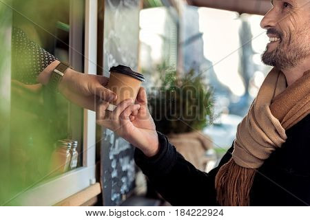 Excited man is taking cup of hot beverage from barista hand. He is looking at salesman with gratitude and smiling. Man is standing outdoors