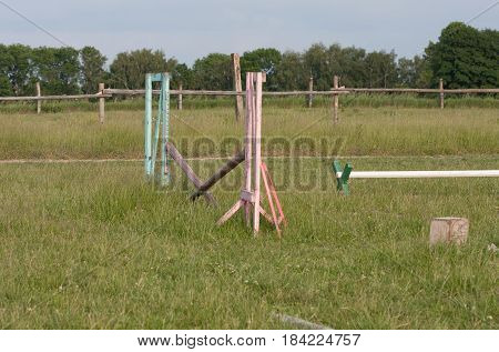 Wooden hurdle for jumping on a horse on meadow in the summer day.