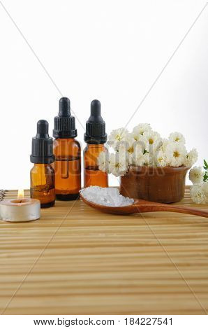 Spa setting with white flower ,towel, oil ,salt in spoon,candle with mat texture