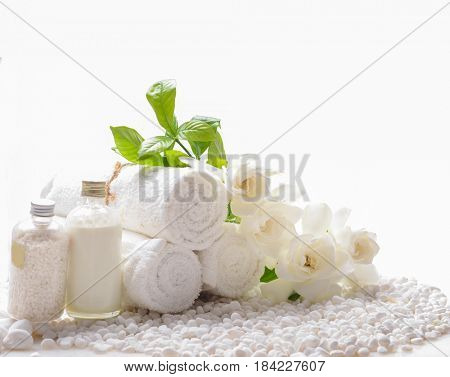 Gardenia's with,massage oil ,rolled towel, on white stones