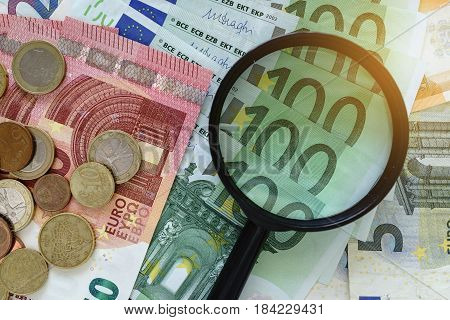 magnifying glass on pile of Euro banknotes with Euro coins as financial analysis concept.