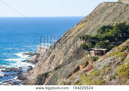 Big Sur USA - March 11 2014: Central California coast with cliffs and blue ocean with house on cliff