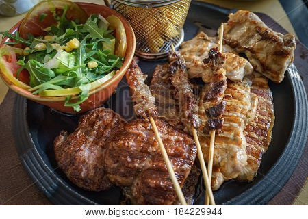 Close up of mixed grilled meat Beef pork poultry with grilled garlic chili pepper and vegetable salad.