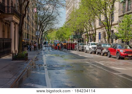 New York NY USA -- April 28 2017 -- Construction workers are busy on a city street near Central park while school children walk down the sidewalk. Editorial Use Only.