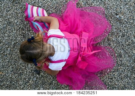 Little girl with a rosy dress gathers pebbles