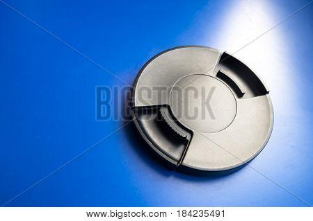 Len cap on blue background. Equipment for camera