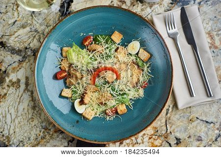 Cesar salad with baked chiken breast served in blue ceramic plate with glass of white wine, fork and spoon on textile napkin on marble table. Top view or flat lay.