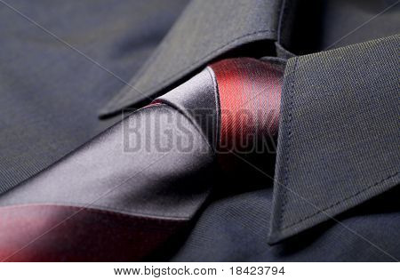 Black business shirt collar with the red and grey necktie