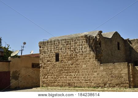 Old house with parabolic antenna close to a ruin with blue sky in background picture from the North of Cyprus.