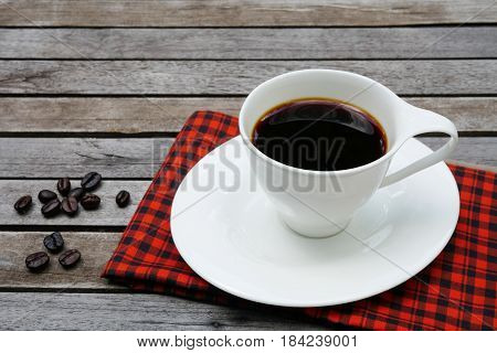 White cup of coffee with coffee beans and red handkerchief on wooden background