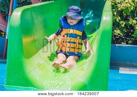 A Boy In A Life Jacket Slides Down From A Slide In A Water Park