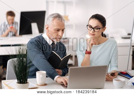 I will explain it. Serious office worker sitting near his coworker holding black notebook in left hand while helping with new program