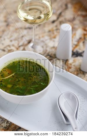 Minestrone soup with arugula served in a white bowl with ceramic spoon, glass of white wine on marble table