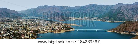Wide panorama of the town of Fujikawaguchiko and Lake Kawaguchi at the foothills of Mount Fuji in Japan