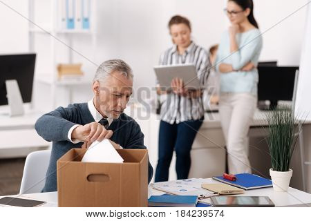 I shall make notes. Serious elderly man bowing head, looking at his table while taking papers from big box
