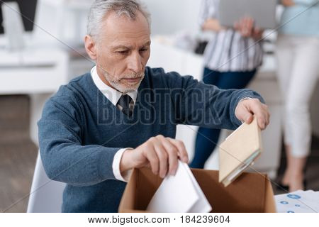 In process. Infatuated office worker wearing blue cardigan holding documents in both hands while wrinkling his forehead