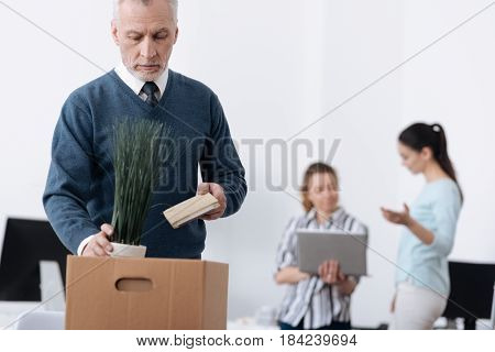 Will go home. Low-spirited man wrinkling his forehead putting plant into box while looking downwards