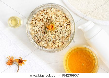Homemade nourishing oatmeal skin care mask: jar of rolled oats, honey, calendula. Top view cosmetic ingredients on light background.