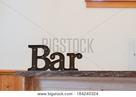 Wedding venue bar sign with black metal and lights on the letters.