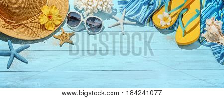 Straw hat, towel, sun glasses and flip flops on blue wooden background