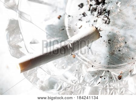 A white cigarette lies in an ashtray .