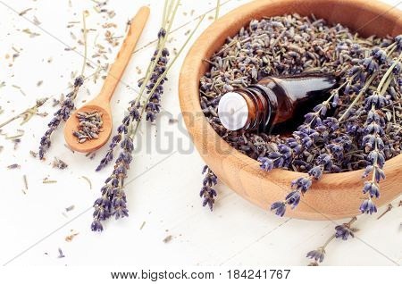 Dropper bottle of aromatic essential oil in wooden bowl full of dried purple lavender herb.