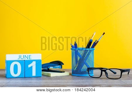 June 1st. Day 1 of month, calendar on business office table, workplace at yellow background. Summer time.