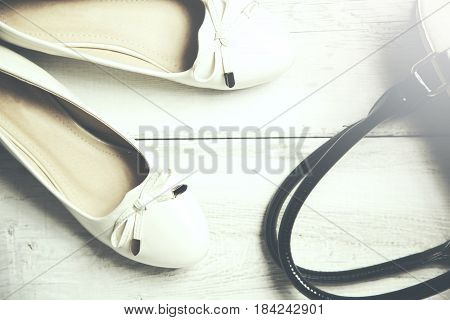 Woman white shoes and bag on wooden background