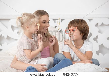 Mother young woman sitting with her children fun with paper masks